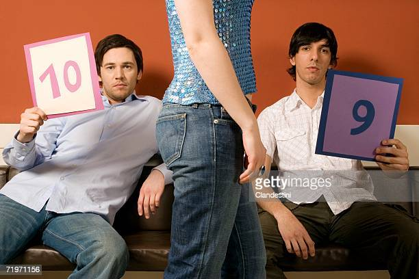 Two young men judging woman