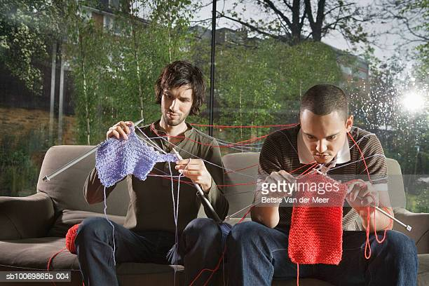 Two young men knitting on sofa in living room