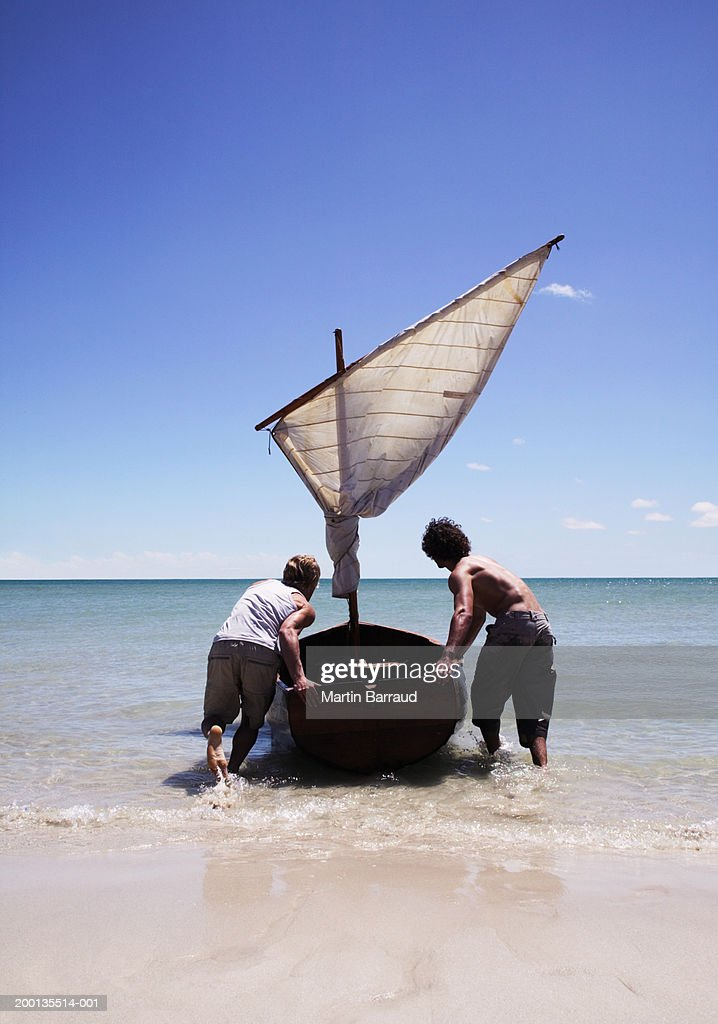 Two young men launching rowing boat to sea, rear view : Stock Photo