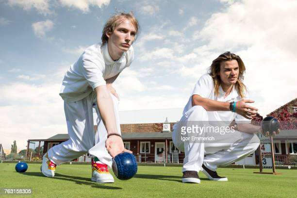 Two young men lawn bowling on bowling green