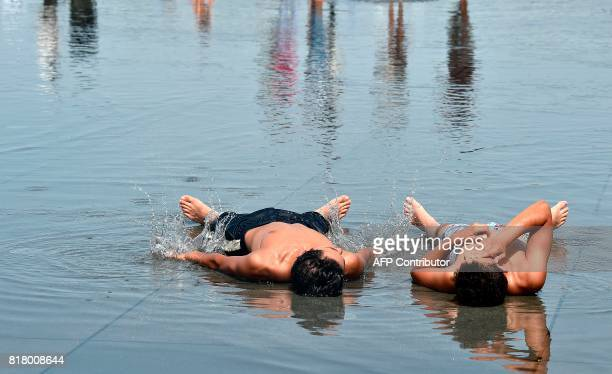 Two young men lie in the water of the 'Mirroir d'eau' a reflecting pool of water in Bordeaux where temperatures came close to 40 C on July 18 2017 /...