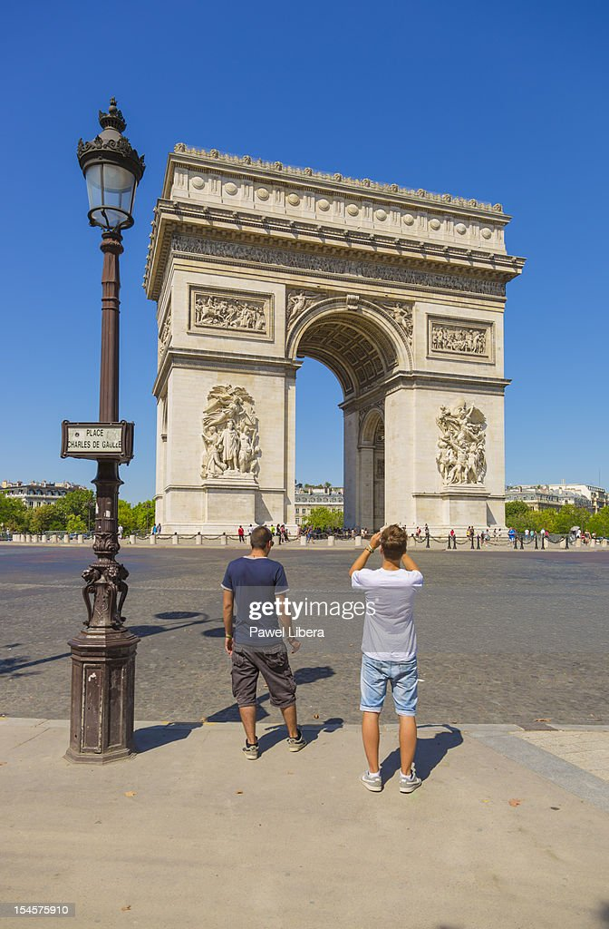 Two young men looking at Arc de Triomphe, Paris : Stock Photo