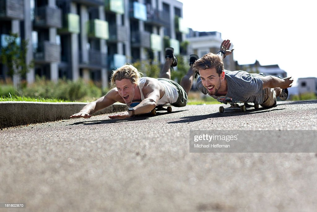 two young men lying on skate boards and racing