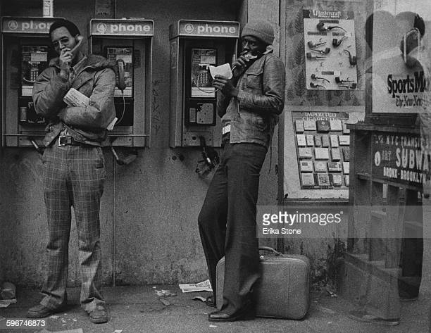Two young men make phonecalls on a payphone by a subway station near Times Square New York City circa 1975