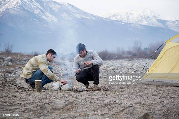Two young men on a river shore  making fire