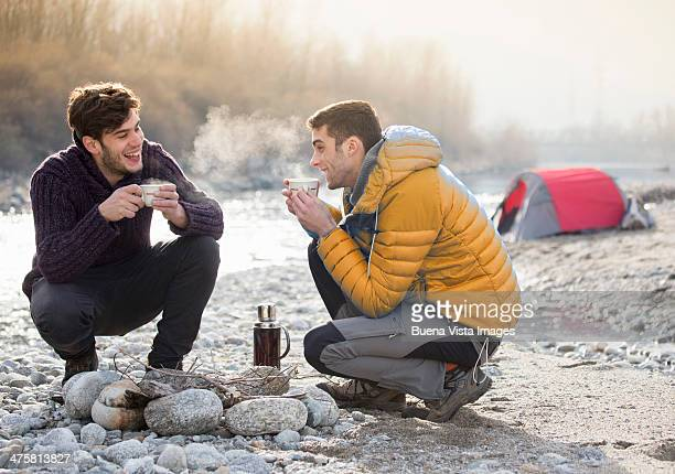 Two young men on a river shore with hot tea