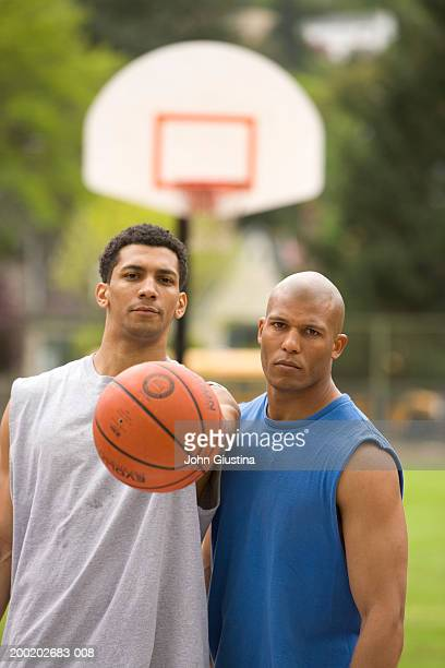 Two young men on basketball court, portrait