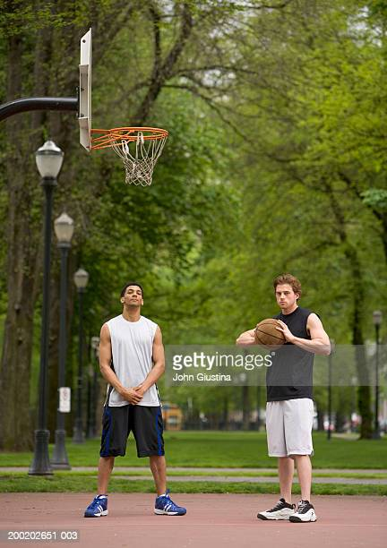 Two young men on court with basketball, portrait