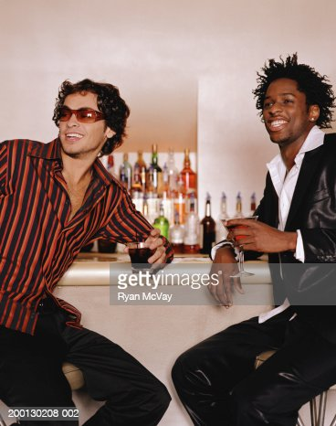 Two young men on stools at bar, smiling : Stock Photo