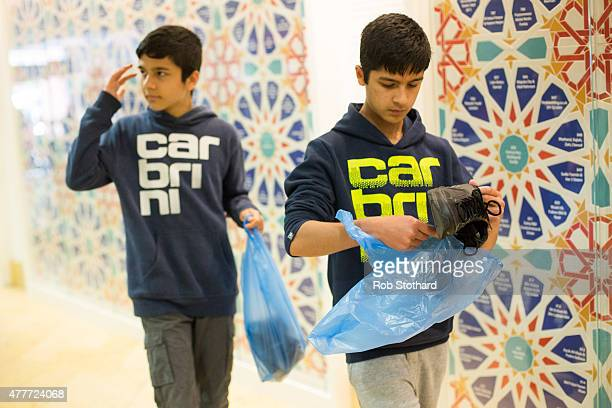 Two young men place their shoes in plastic bags upon arriving East London Mosque to attend the first Friday prayers of the Islamic holy month of...