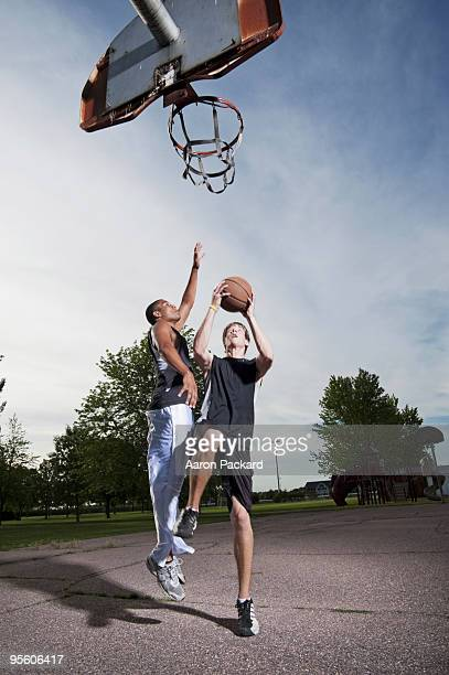 Two young men play one on one Basketball at Barstow Park in Vermillion, South Dakota (lit with flash