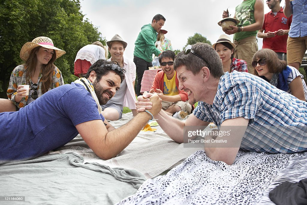 Two young men playing arm wrestle in the park : Stock Photo