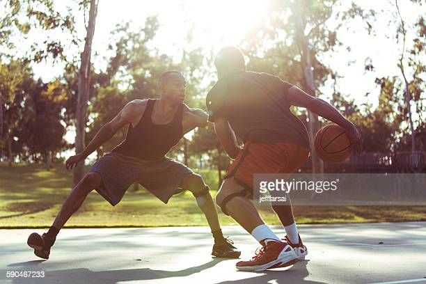 Two young men playing basketball in the park at sunset