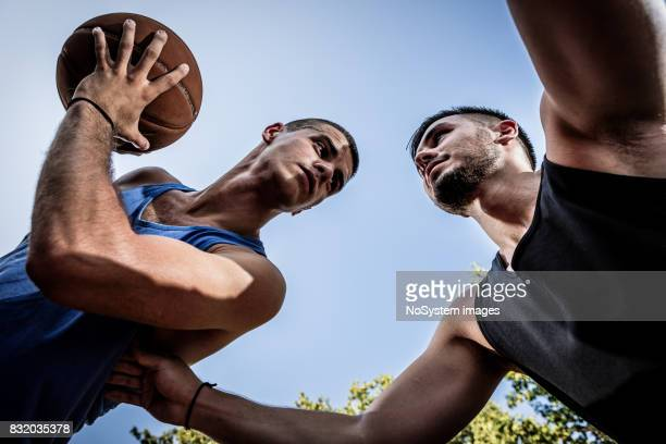 Two young men playing basketball on outdoor court
