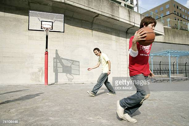 Two young men playing basketball