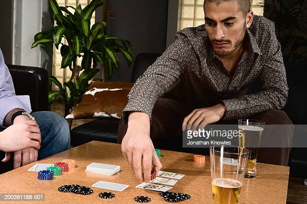 Two young men playing poker, one placing chips in game's pot