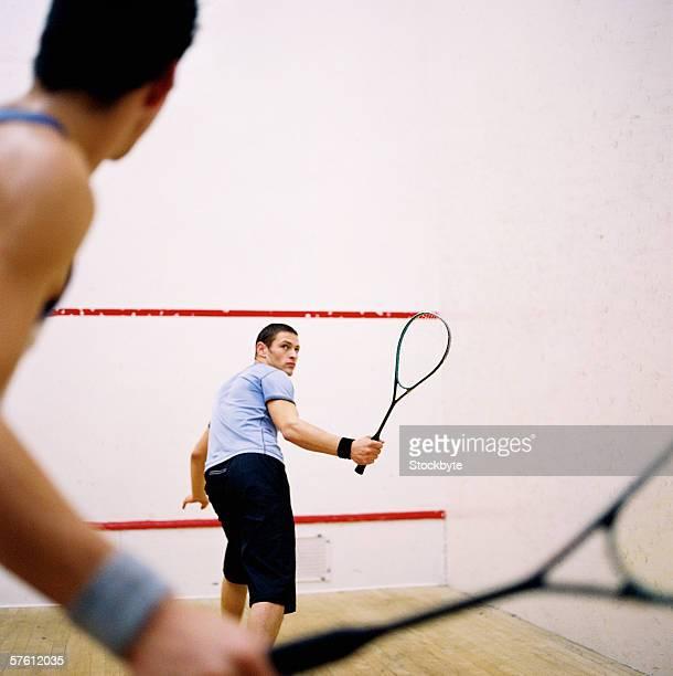 Two young men playing squash