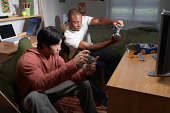 Two young men playing video game in dorm room, side view