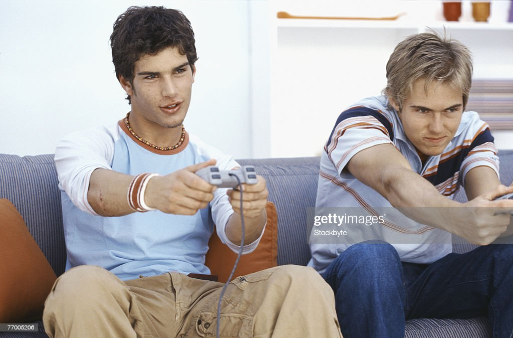 Two young men playing video games in living room : Stock Photo
