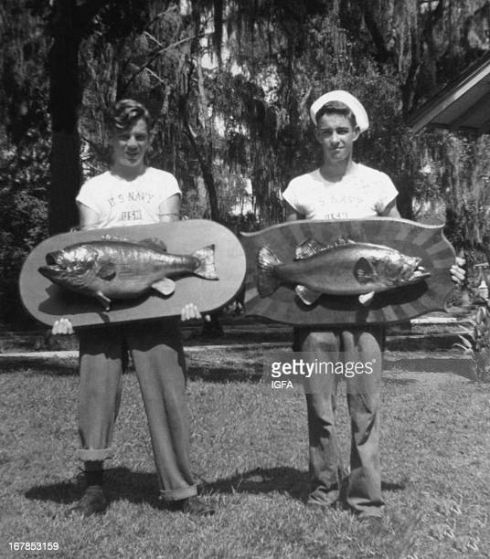 Two young men pose on the lawn holding mounted largemouth bass caught in Florida in the United States on July 24 1945