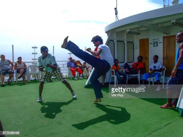 Two young men practice capoeira a Brazilian martial art form on the ferry from Santo Antao to Sao Vicente Republic of Cabo Verde Africa