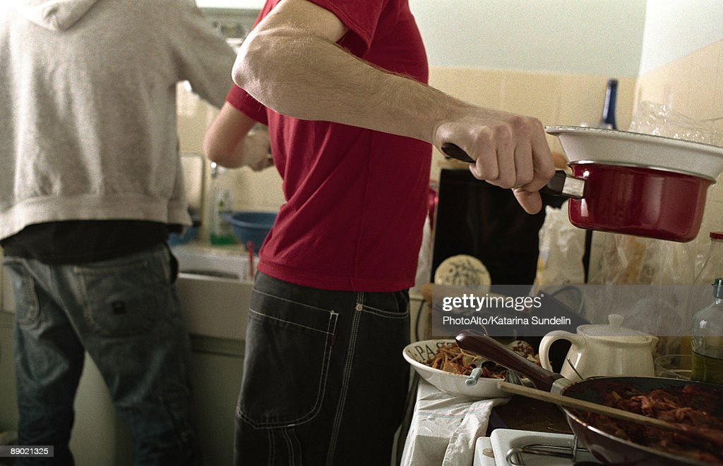 Two young men preparing food in kitchen : Stock Photo