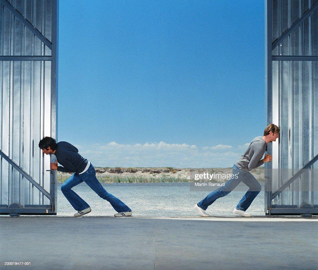 Two young men pushing warehouse doors open
