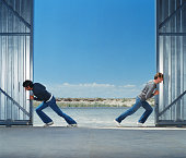 Two young men pushing warehouse doors open