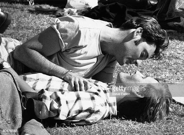 Two young men sharing a tender moment on the grass during a Gay Pride festival in London 1996
