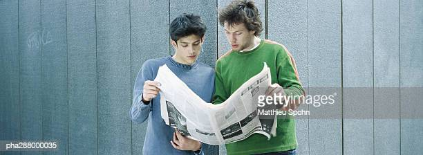 Two young men sharing newspaper