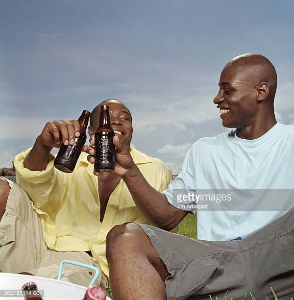 Two young men sitting in grass, toasting with beer bottles