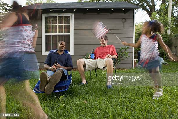 Two young men sitting on lawn chairs enjoying a beer while daughters play