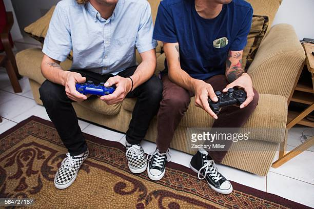 Two young men sitting on sofa, playing video game, low section