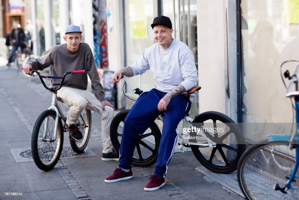 two young men sitting on their bicycles in city : Stock Photo
