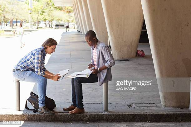 Two young men sitting outside building studying