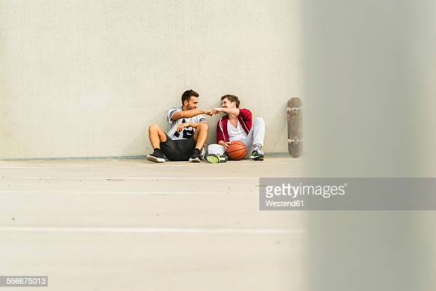 Two young men sitting with skateboard and basketball on parking level