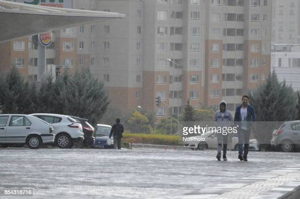 Two young men smile as they walk on a raindrenched road during a rainy autumn day in Ankara Turkey on September 26 2017 The temperature in Ankara...