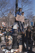 Two young men stand on a fence and lean against a lamppost next to an overfull garbage can in Union Square during the first Earth Day celebration New...