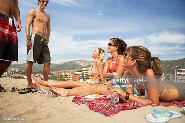 Two young men standing by three young women lying on beach