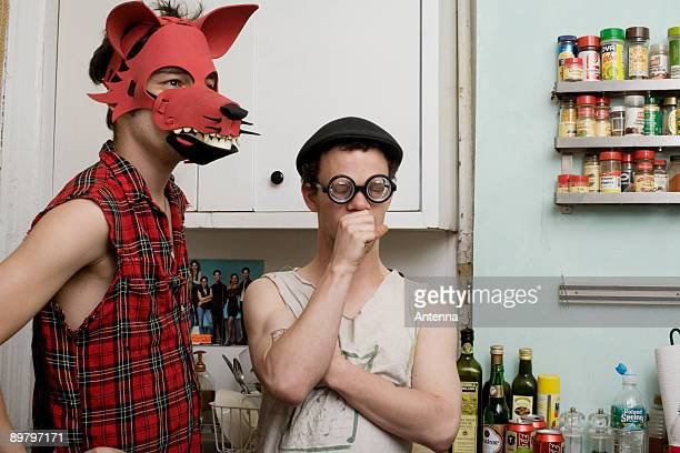 Two young men standing in a kitchen wearing silly disguises