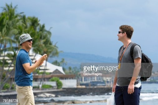 Two young men standing on the beach, Kona, Big Island, Hawaii Islands, USA : Stock Photo