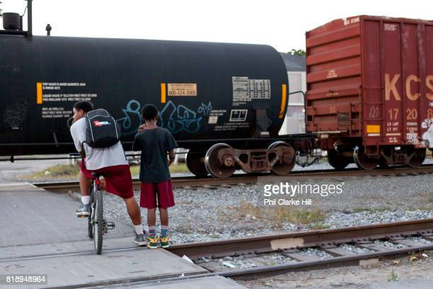 Two young men swaiting for a train to pass at a level crossing in New Orleans Louisiana USA walking down the street in the French Quarter