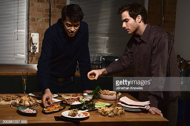 Two young men taking food from buffet