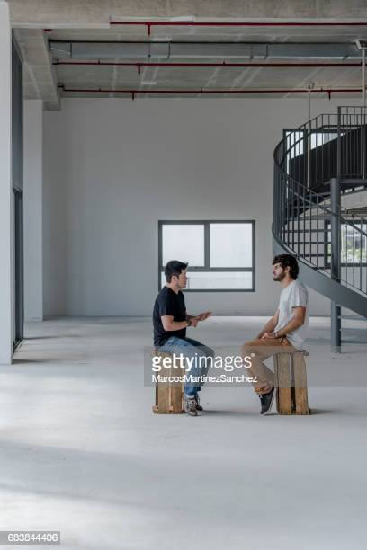 Two young men talking in an empty office