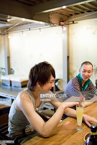 Two young men talking over a counter