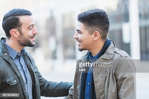 Two young men talking, shaking hands : Stock-Foto