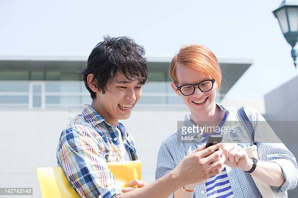 Two young men using Smartphone at campus