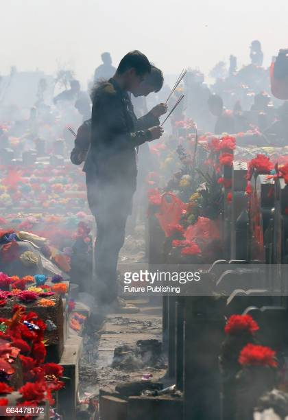 Two young men visit a tomb in a cemetery on the occasion of the traditional TombSweeping Festival on April 04 2017 in Jinjiang China Feature China /...