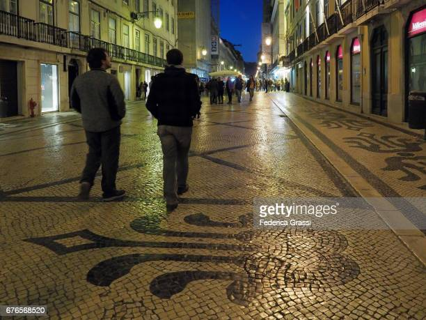 Two Young Men Walking At Night In Lisbon, Portugal