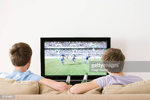 Two young men watching football on the tv